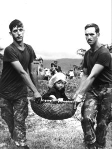 6th July 1970:  Two American marines carrying a young Vietnamese refugee in a basket during the evacuation of a village near Da Nang.  (Photo by Keystone/Getty Images)