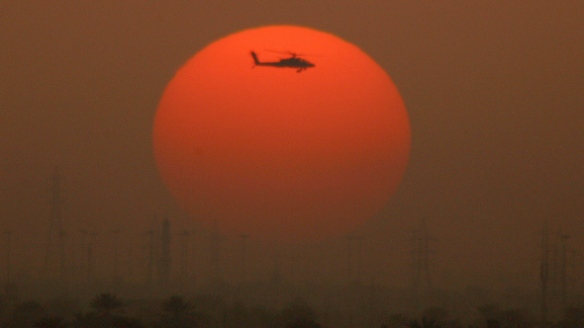 A US army Apache helicopter flies over Baghdad as the sun sets, 21 March 2007. Eleven people were killed and dozens  wounded in separate attacks in and around the Iraqi capital Baghdad on Wednesday, security officials said. AFP PHOTO/PATRICK BAZ